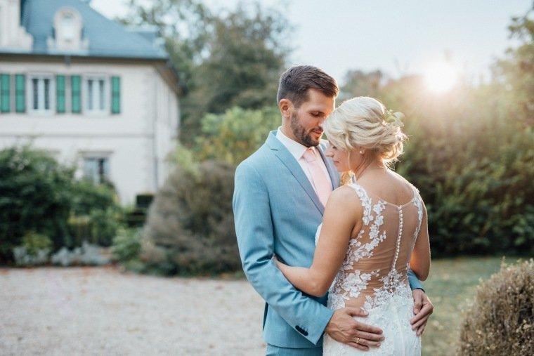 Hochzeitsfotos-Landgut-Schloss-Michelfeld-Hochzeitsreportage-Angelbachtal-028-Brautpaar-Tattoospitze-Sonnenuntergang-hellblauer-Anzug