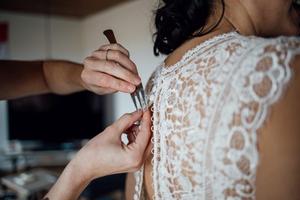Braut zieht Brautkleid an Getting Ready Gabel