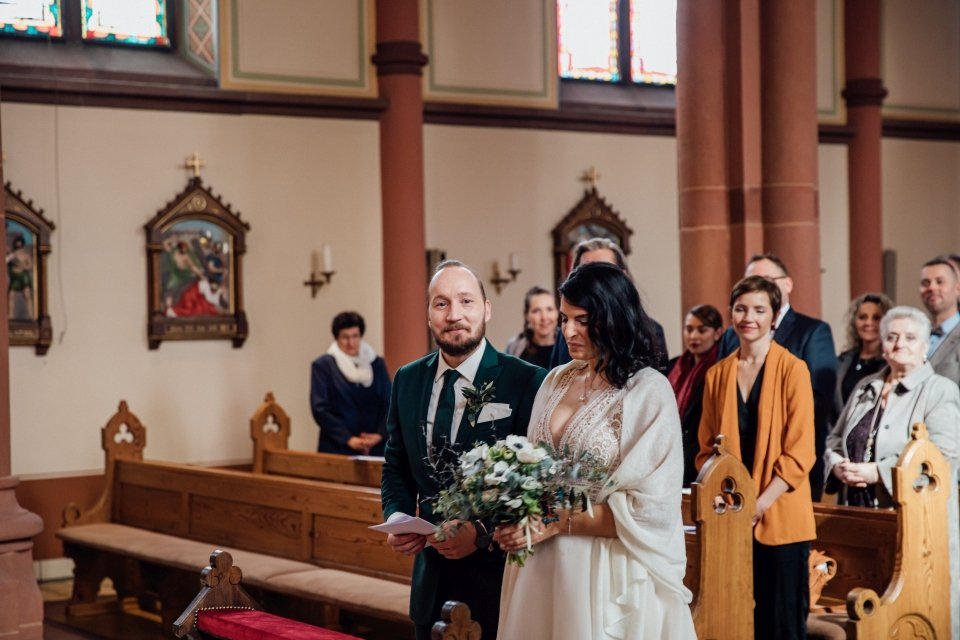 Braut mit Brautstrauß in der Kirche bei Winterhochzeit