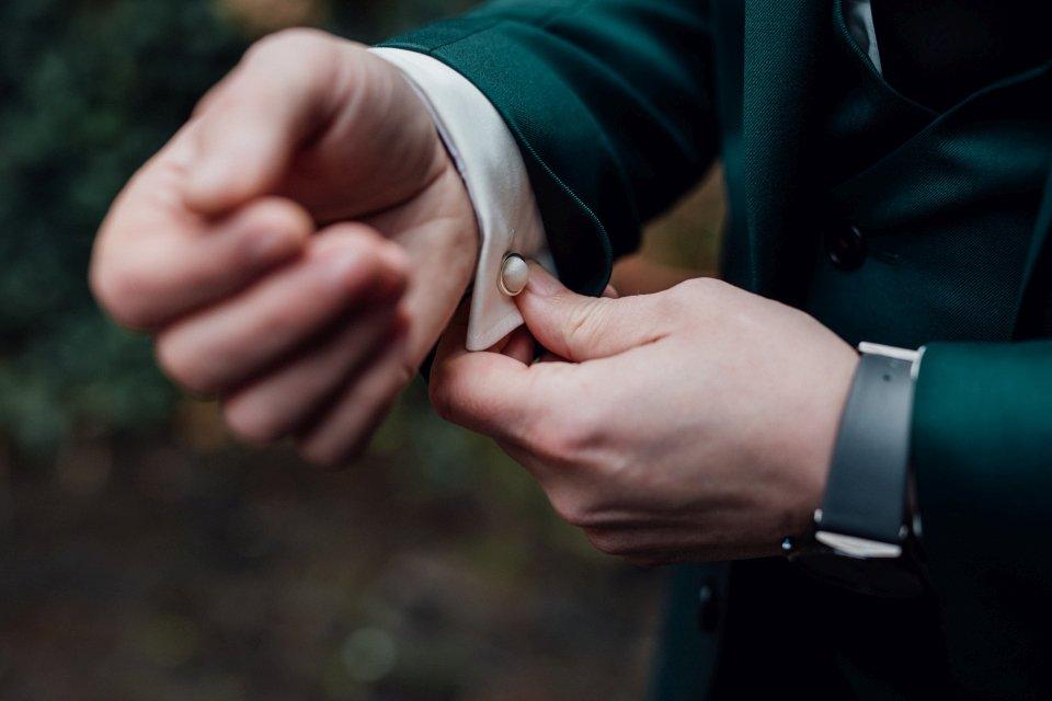 Bräutigam mit Manschettenknöpfen und grüner Hochzeitsanzug