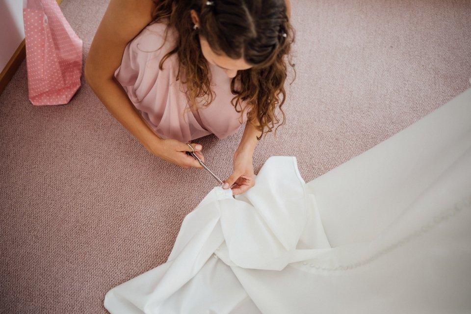 Sommerhochzeit-Hochzeitsreportage-043-Brautjungfer-repariert-brautkleid-getting-ready